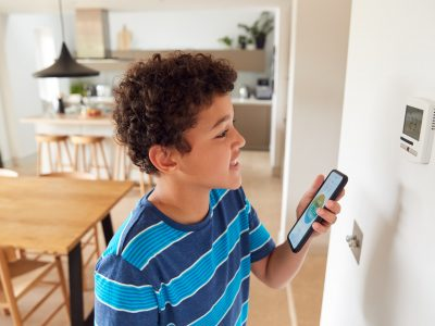 Boy Changes Temperature On Central Heating Thermostat Control Using Mobile Phone App